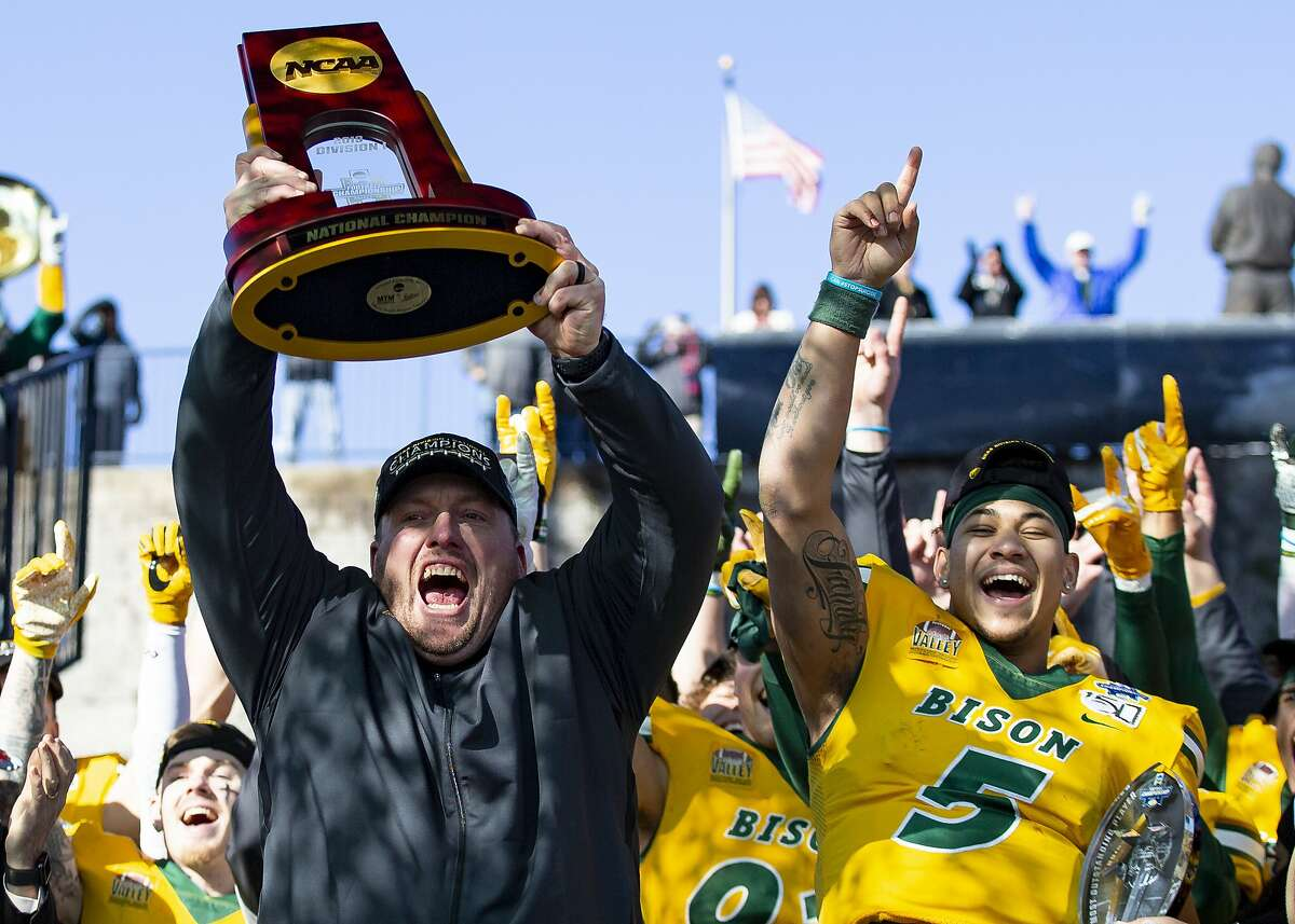FILE - In this Jan. 11, 2020, file photo, North Dakota State head coach Matt Entz raises the trophy alongside quarterback Trey Lance (5) as they celebrate after beating James Madison 28-20 in the FCS championship NCAA college football game in Frisco, Texas. Entz says the benefits of practicing for a one-game season this year, outweighed the risks and frustration from dealing with the coronavirus. The Bison have been practicing for the last month ahead of Saturday's game against Central Arkansas. (AP Photo/Sam Hodde, File)