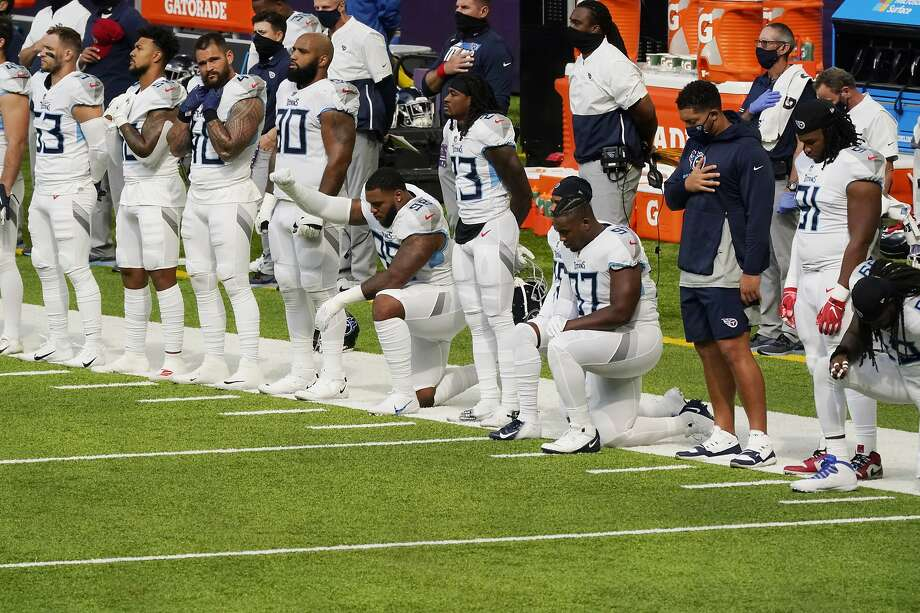Members of the Tennessee Titans take part in the national anthem before an NFL football game against the Minnesota Vikings, Sunday, Sept. 27, 2020, in Minneapolis. The NFL says the Tennessee Titans and Minnesota Vikings are suspending in-person activities after the Titans had three players test positive for the coronavirus, along with five other personnel. The league says both clubs are working closely with the NFL and the players' union on tracing contacts, more testing and monitoring developments. The Titans are scheduled to host the Pittsburgh Steelers on Sunday.(AP Photo/Jim Mone) Photo: Jim Mone / Associated Press