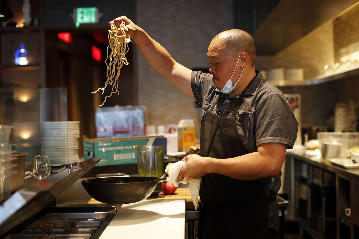 Chef Rob Lam prepares a dish with garlic noodles at Lily in San Francisco. Lily is opening on Oct. 1.