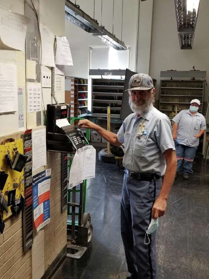 Longtime postal employee Roger Stambaugh clocks out of work after a busy day of delivering Plainview mail for the last time. Photo: Ellysa Harris/Plainview Herald
