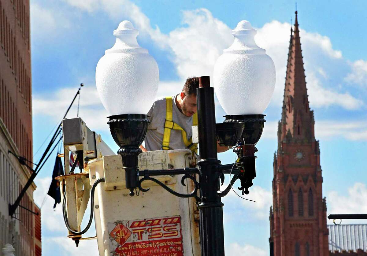 A worker is seen in a bucket truck fixing a light outside City Hall on Thursday, Oct. 1, 2020 in Albany, N.Y. (Lori Van Buren/Times Union)