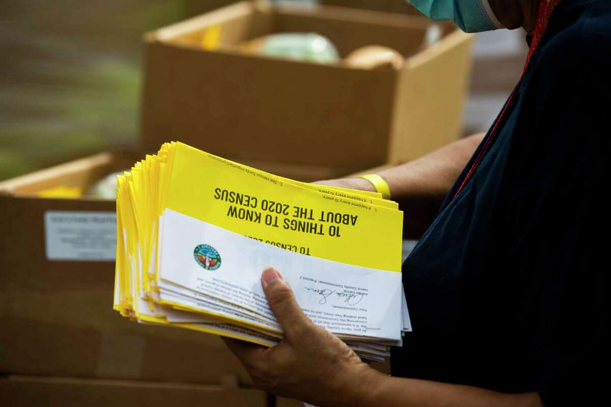 Vanessa Barnes holds flyers with information about the 2020 Census at a food drive event organized by Hobby Area District, Friday, Sept. 18, 2020, in Houston.