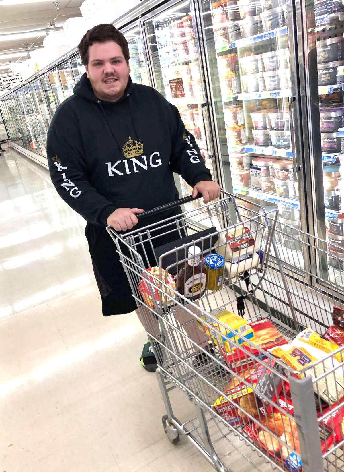 Tyler Joseph, 21, of Big Rapids, flashes a smile for the camera during a recent grocery shopping trip. For the last couple of months, Joseph has been buying groceries for those in need out of a random act of kindness. Joseph said he's happy he can help support a community that supported him during difficult times in his life.