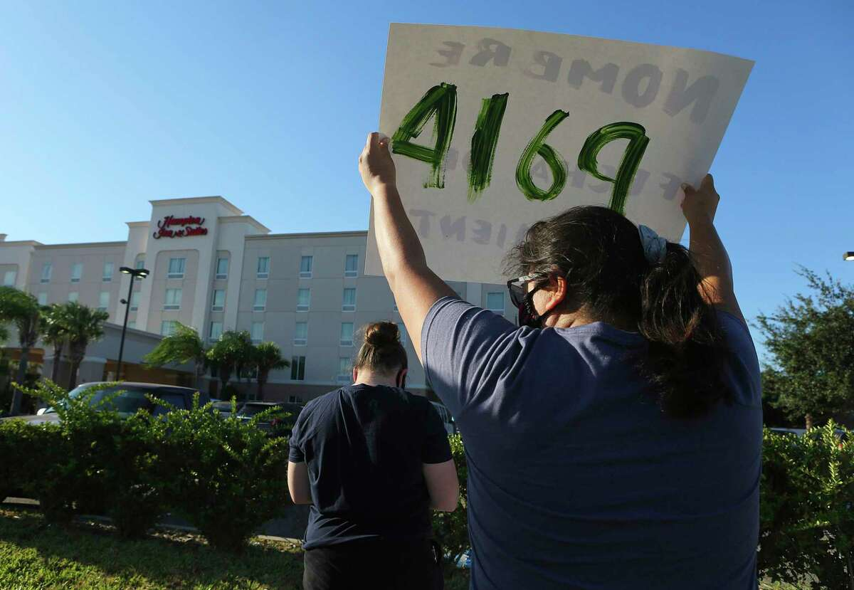Protesters wave signs in front of the Hampton Inn hotel on Thursday, July 23, 2020, in McAllen, Texas. The government is seeking to halt an order barring officials from using a COVID-19 loophole to detain children, toddlers and infants in hotels before expelling them to their home countries.