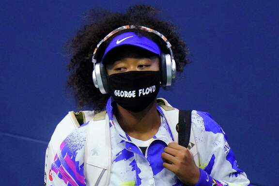 """In this Sept. 8, 2020, file photo, Naomi Osaka, of Japan, wears a protective mask due to the COVID-19 virus outbreak, featuring the name """"George Floyd,"""" while arriving on court to face Shelby Rogers, of the United States, during the quarterfinal round of the US Open tennis championships, in New York. Osaka's victory in the U.S. Open helped raised the issue of racial injustice in the United States. Before each of her matches, she wore a mask with the names of seven Black Americans who died as victims of violence."""