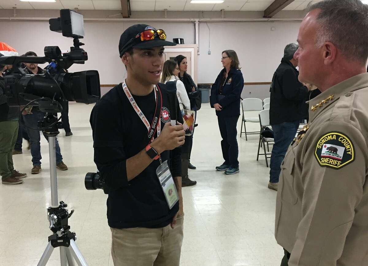 San Rosa Junior College student Nick Vides, editor of the Oak Leaf newspaper, interviews Sonoma County Sheriff Mark Essick in 2020.