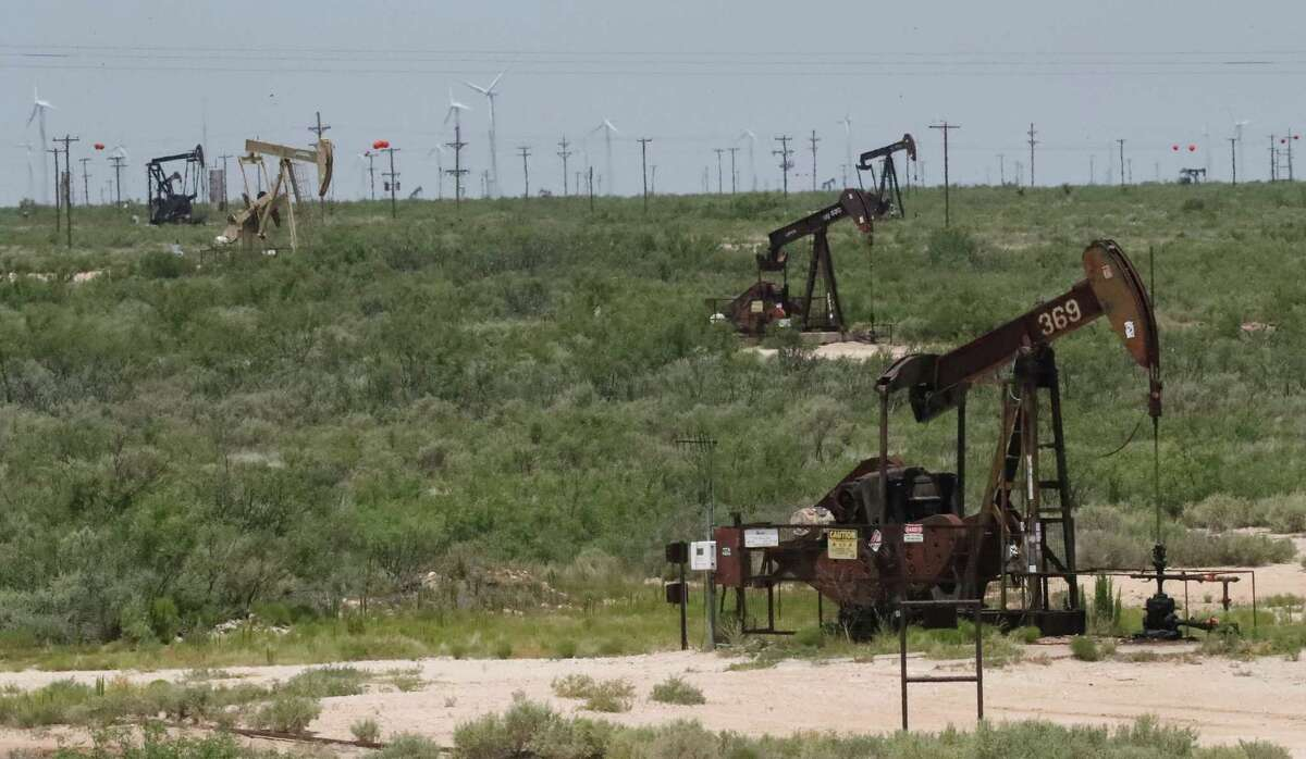 Pump jacks are stacked in front of rows of a windmill field in West Texas Wednesday, June 28, 2017 outside of Kermit, Texas. ( Steve Gonzales / Houston Chronicle )