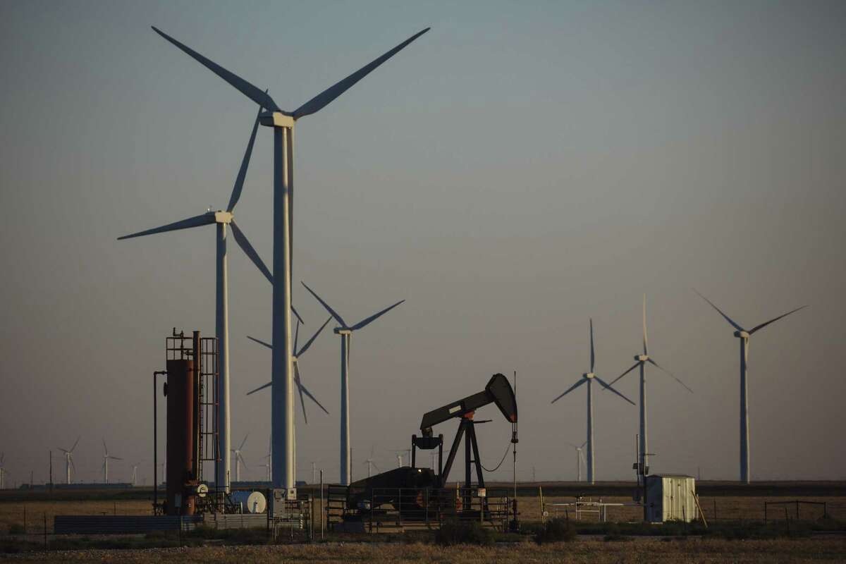 A pump jack stands next to wind turbines near Guymon, Oklahoma, U.S., on Friday, Sept. 25, 2020. After all the trauma the U.S. oil industry has been through this year -- from production cuts to mass layoffs and a string of bankruptcies -- many producers say they're still prioritizing output over reducing debt. Photographer: Angus Mordant/Bloomberg
