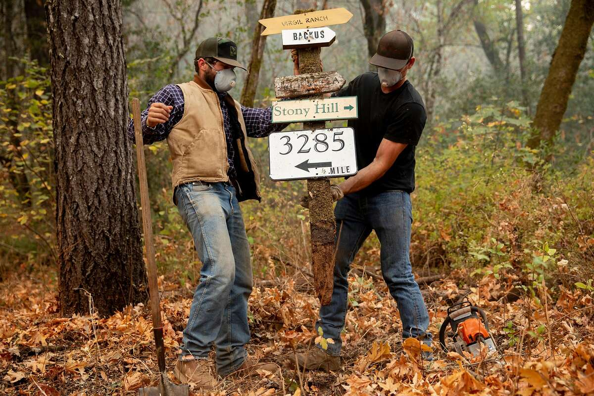 Russell Tobiass (left) and Matteo Abreu of David Abreu Vineyard Management work to remove a road sign and clear brush to allow water trucks to access Stony Hill Vineyard as the Glass Fire burns on its Spring Mountain property.