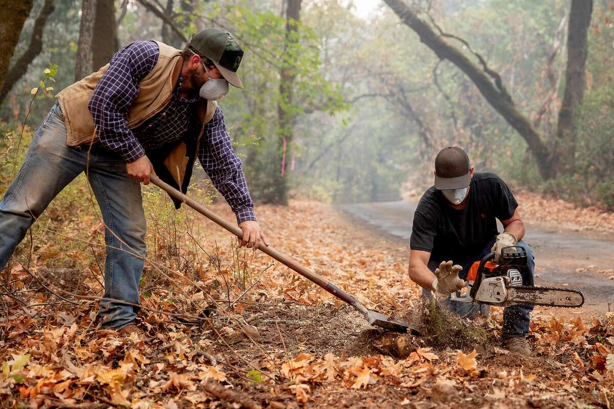 Russell Tobiass (left) and Matteo Abreu of David Abreu Vineyard Management work to clear brush from a road to allow water trucks to access Stony Hill Vineyard as the Glass Fire burns on its property on Spring Mountain.