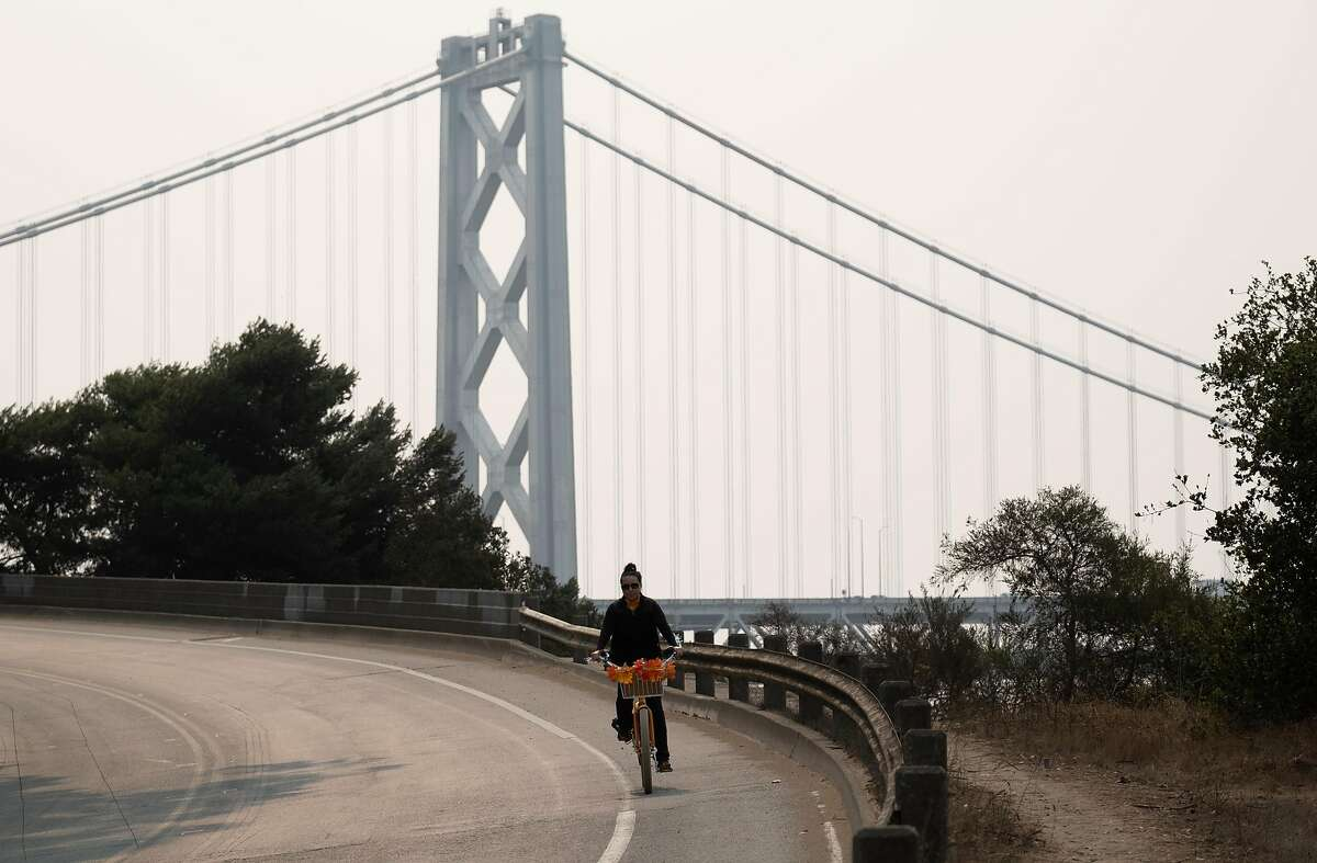 A bicyclist rides down the road with the Bay Bridge obscured by wild fire smoke on Treasure Island, Thursday, October 1, 2020. There is a spare the air alert in affect through Tuesday as smoke from the recent wildfires descends on the Bay Area.