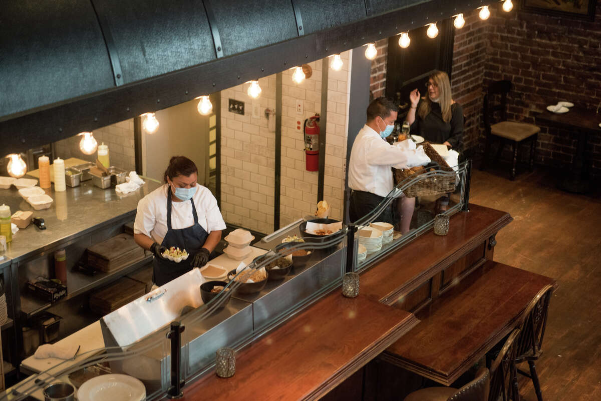 Wayfare Tavern, at 558 Sacramento St., once again offers indoor dining, with a few changes. Staff can be seen through the open kitchen wearing masks and gloves, as a diner eats lunch indoors in the corner.
