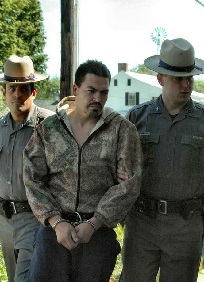 Abel Jimenez is walked away from a Brunswick farm by State Police. (IPA / Special to the Times Union)