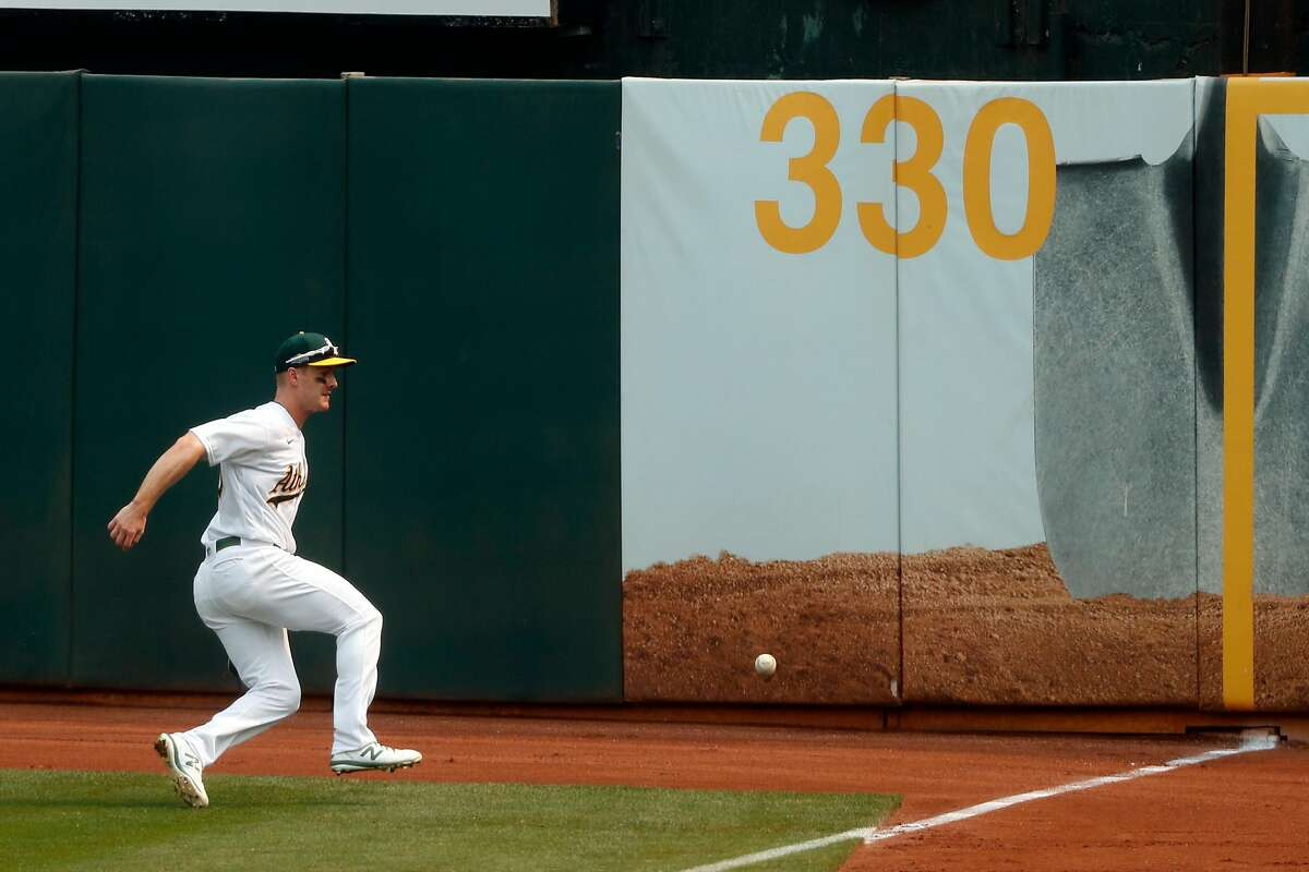 Oakland Athletics' Mark Canha chases down a double by Chicago White Sox' Tim Anderson in 2nd inning during Game 3 of Wild Card Series at Oakland Coliseum in Oakland, Calif., on Thursday, October 1, 2020.