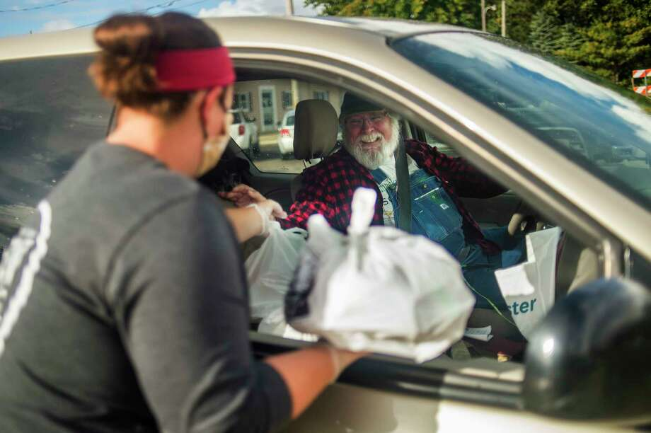 Karl Kacel of Sanford, right, smiles as Andrea Secrease of Midland, left, passes him hot meals during a food distribution event Thursday evening at Cole's Wrecker Service and Garage in Sanford. A group of volunteers is serving the hot meals, donated by local businesses and individuals, twice weekly to Sanford residents who have been impacted by the mid-Michigan dam failures and flooding in May. For more photos, visit www.ourmidland.com. (Katy Kildee/kkildee@mdn.net)
