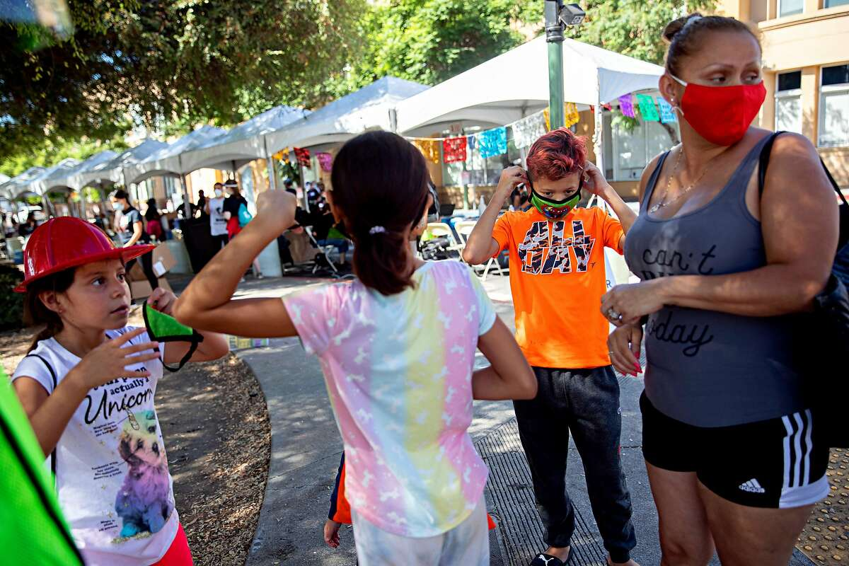 Hailey Gomez, 7 (left), Barbie Gomez, 9, Elkin Gomez, 12, and their mother, Patricia Gomez, line up for free coronavirus tests in Oakland's predominantly Latino Fruitvale neighborhood last month.