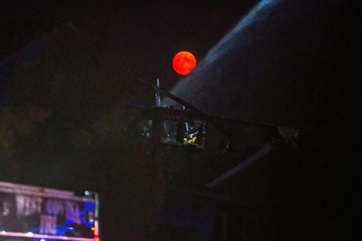 The moon rises over firefighters helping to put out whats left of the Glass Fire in the Skyhawk neighborhood on September 30, 2020 in Santa Rosa, CA.