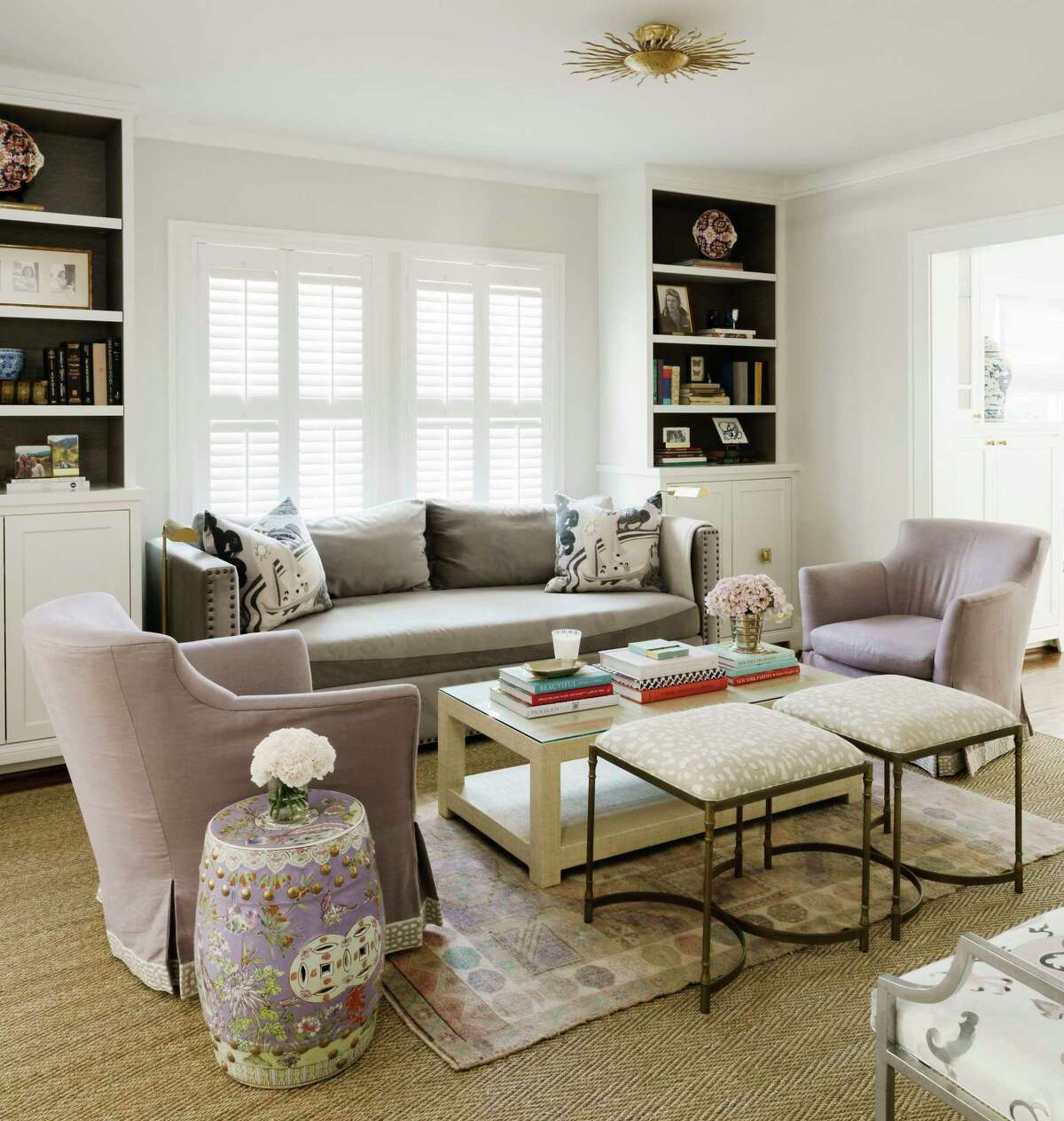 Interior designer Hallie Sims of Hallie Henley Design packed a lot into Clair Hedgcoxe's small living room: a sofa, two chairs and two stools for extra seating.