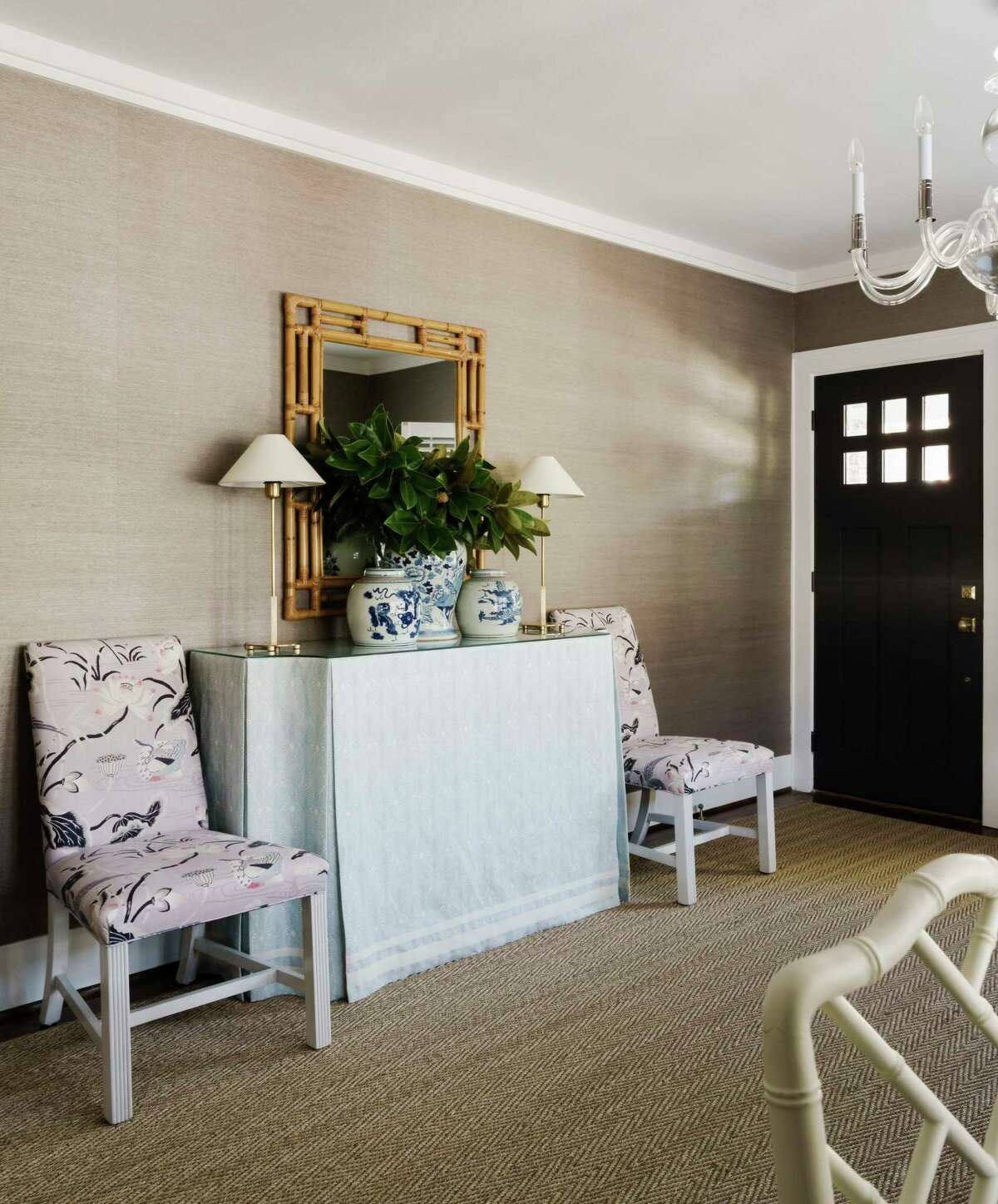 The home didn't have a formal foyer, so they created a foyer effect by plasing a hall table with a pair of chairs and other decor just inside the front door.
