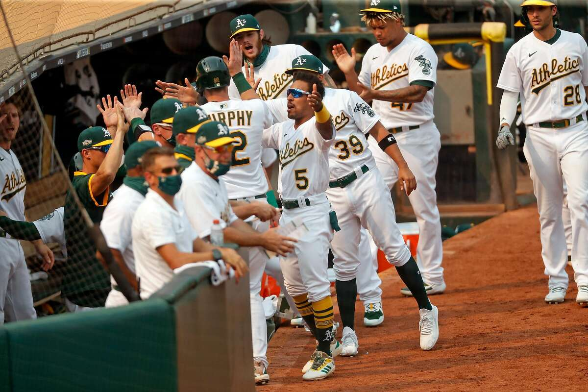 Oakland Athletics' Sean Murphy and Tommy La Stella are welcomed back to the dugout after 2-run single by Chad Pinder in 5th inning against Chicago White Sox during Game 3 of Wild Card Series at Oakland Coliseum in Oakland, Calif., on Thursday, October 1, 2020.