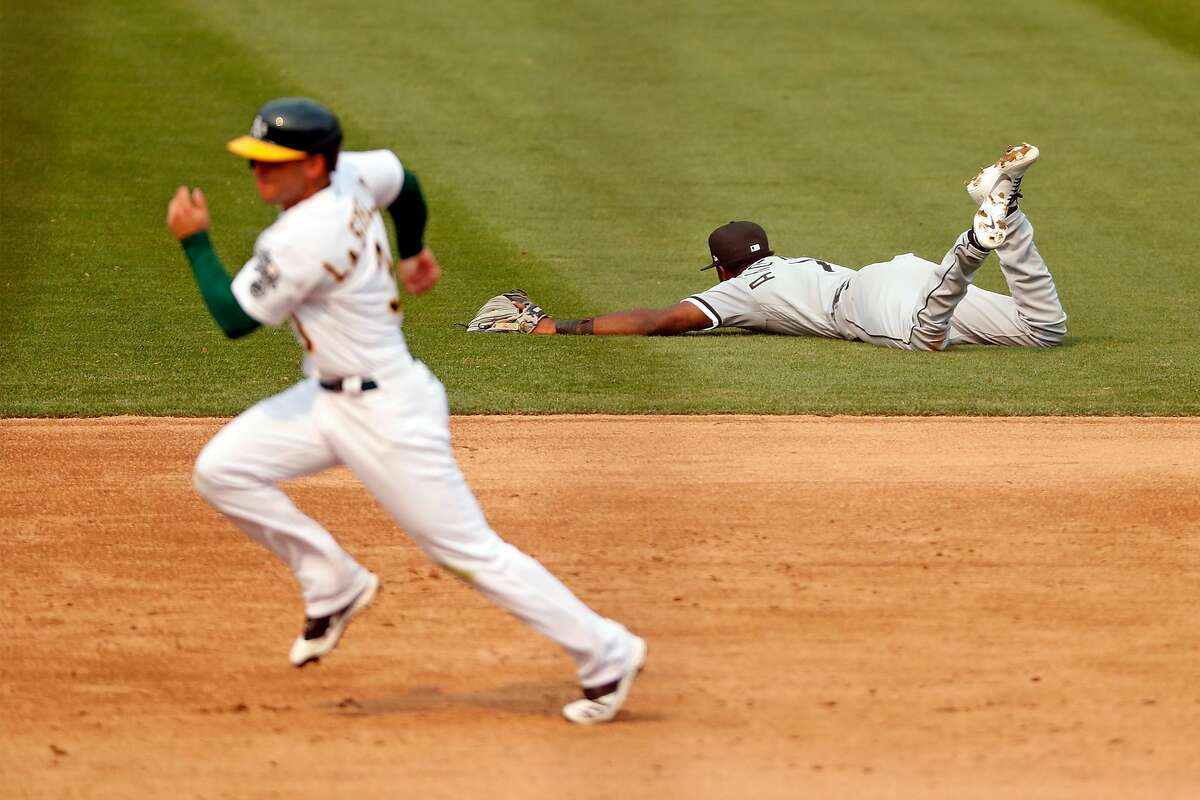 As Oakland Athletics' Tommy la Stella heads for home, Chicago White Sox' Tim Anderson can't stop Chad Pinder's 2-run single in 5th inning against Coliseum in Oakland, Calif., on Thursday, October 1, 2020.