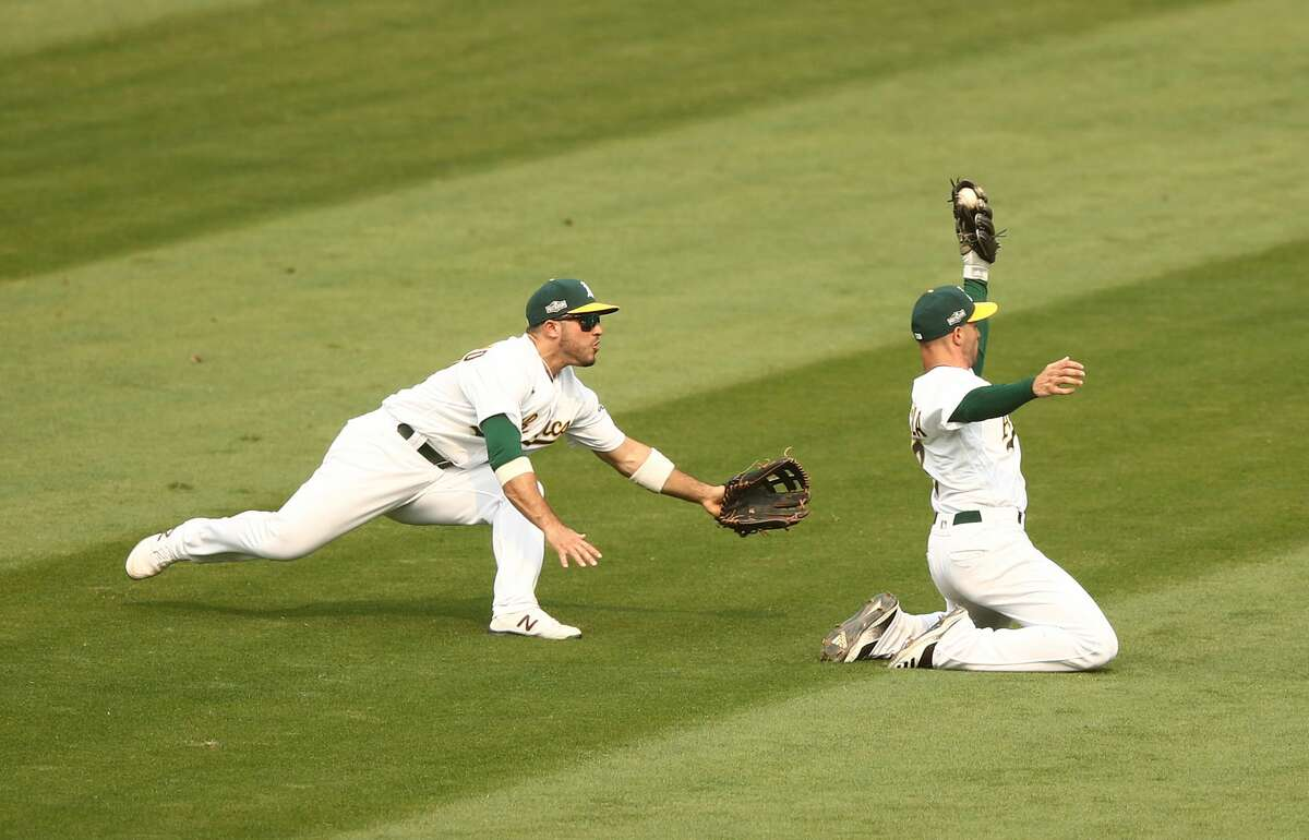 Tommy La Stella, right, of the Oakland Athletics makes a great catch on a ball hit by Adam Engelof the Chicago White Sox as Ramon Laureano watches him in the fifth inning of Game 3 of the American League wild card series at RingCentral Coliseum.