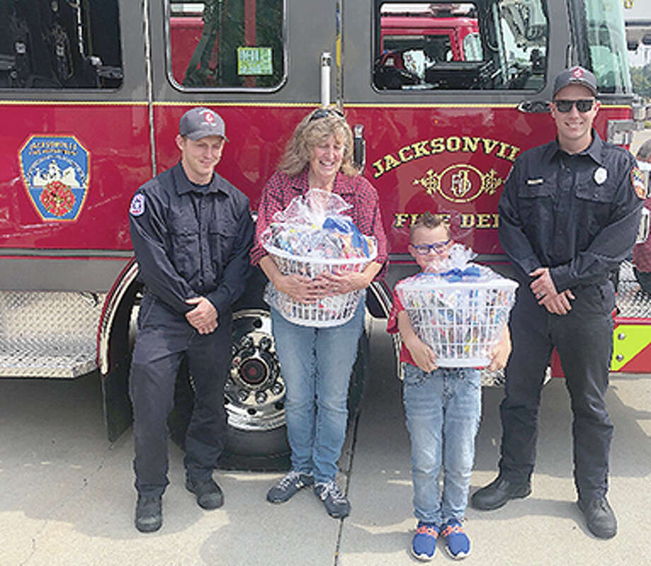 Jacksonville Fire Department members accept gift baskets presented by Buchheit retail department manager Sue Radkiewicz and her grandson, Jackson. Photo: Photo Provided