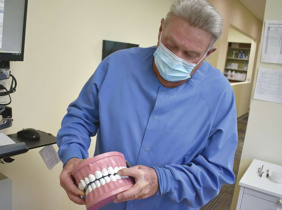 Dr. Michael Watkins of Midwest Dental demonstrates how teeth can grind together without a person being aware it's happening. As dentists report a nationwide surge of cracked teeth, Watkins says stress can lead to more grinding. Photo: Marco Cartolano | Journal-Courier