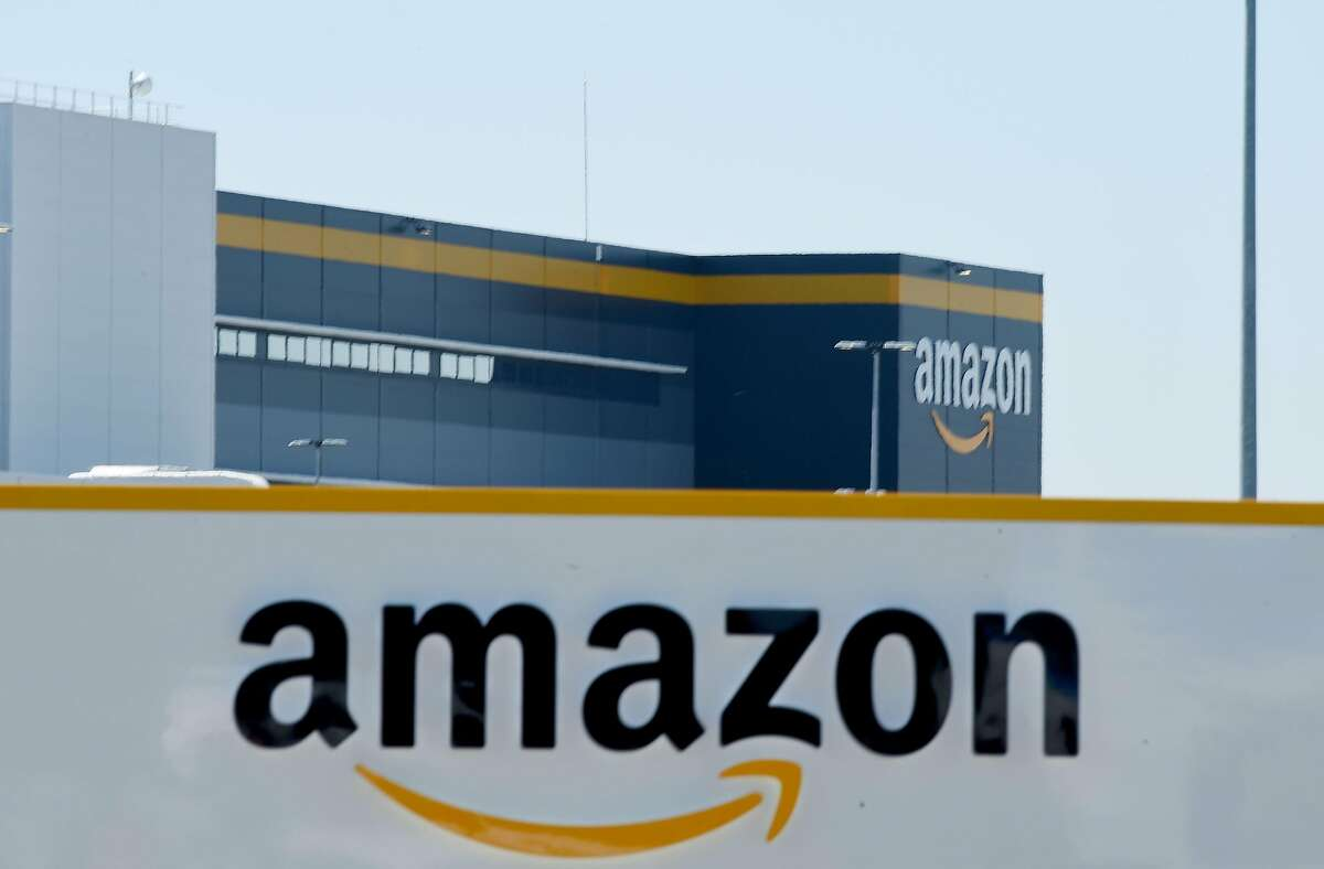 (FILES) In this file photo taken on May 19, 2020 in Bretigny-sur-Orge on May 19, 2020 shows a sign with the company's logo at Amazon's centre entrance as Amazon France partially reopens amid the pandemic of the novel coronavirus (COVID-19). - Amazon on September 29, 2020, defended its warehouse safety record after a news investigation pointed to a higher-than-average injury rate in the company's massive logistics operations. (Photo by ERIC PIERMONT / AFP) (Photo by ERIC PIERMONT/AFP via Getty Images)