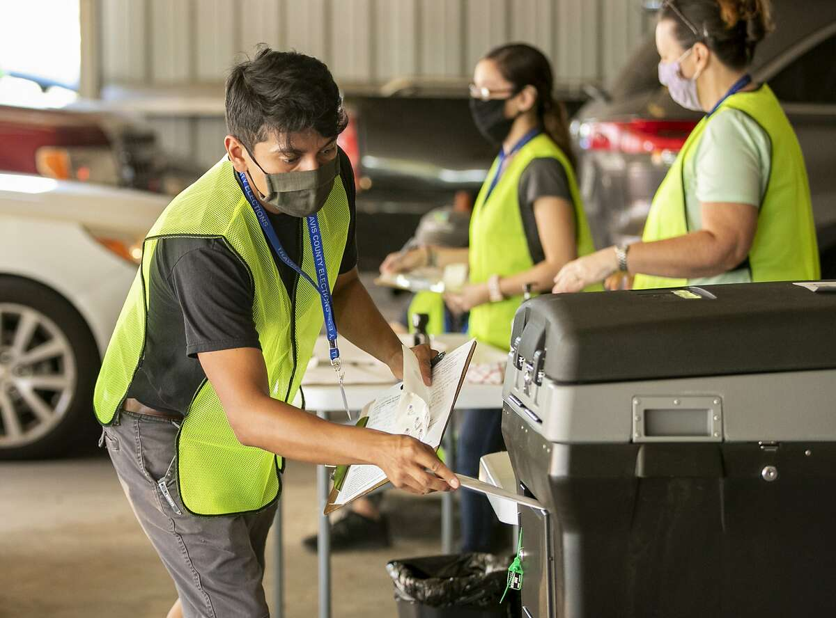 Delivery clerk Mark Garcia deposits a ballot in a box at a drive-through drop-off location in Austin, Texas.