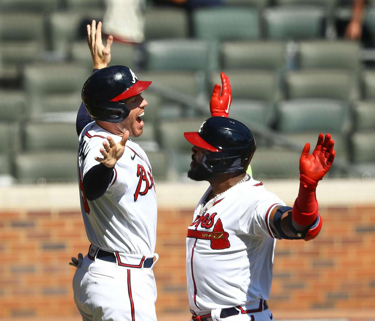 Atlanta Braves Marcell Ozuna, right, gets a double hive five from Freddie Freeman, left, as they celebrate Ozuna hitting a 2-run homer to take a 3-0 lead over the Reds during the 8th inning of Game 2 in the National League wild card playoff series on Thursday, Oct 1, 2020 in Atlanta. The Braves beat the Reds 5-0 for the two game sweep to advance. (Curtis Compton/Atlanta Journal-Constitution/TNS)