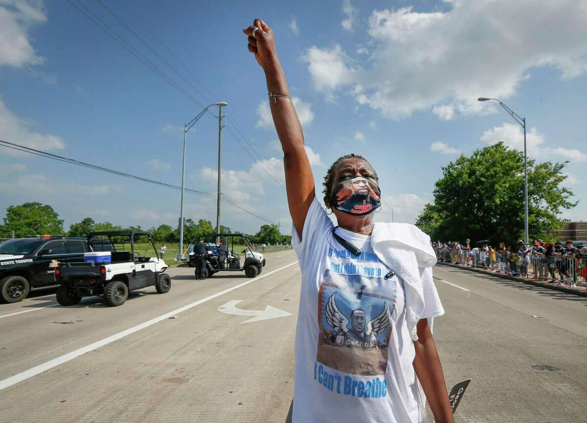 Debra Baines shouts George Floyd's name from the median of Cullen Road, as she watched the remains of George Floyd brought to Silverlake Community Church to be transferred to a horse-drawn carriage Tuesday, June 9, 2020, in Pearland, Texas. (Steve Gonzales/Houston Chronicle via AP)