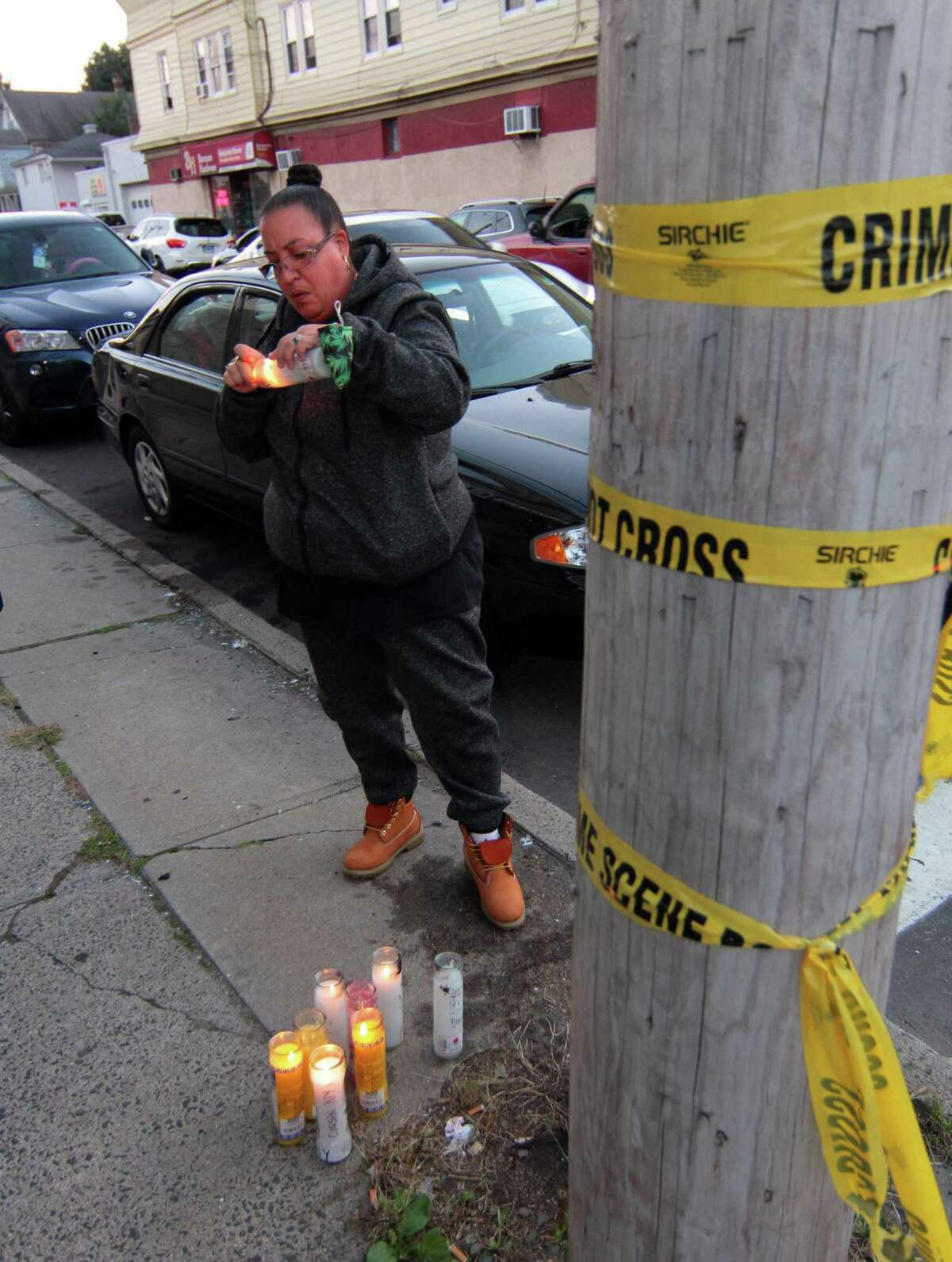 Saida Duberry lights candles at a memorial set up for Nyair Charles Nixon Jr. outside the now shuttered Keystone Mens Club on Barnum Avenue in Bridgeport, Conn., on Thursday Oct. 1, 2020. Some 60 people gathered outside the Keystone to demand the FBI take over the investigation and look into the actions of Bridgeport City Council Member Eneida Martinez, who manages the club were Nixon was shot before stumbling into the street where he was struck by a fleeing car.