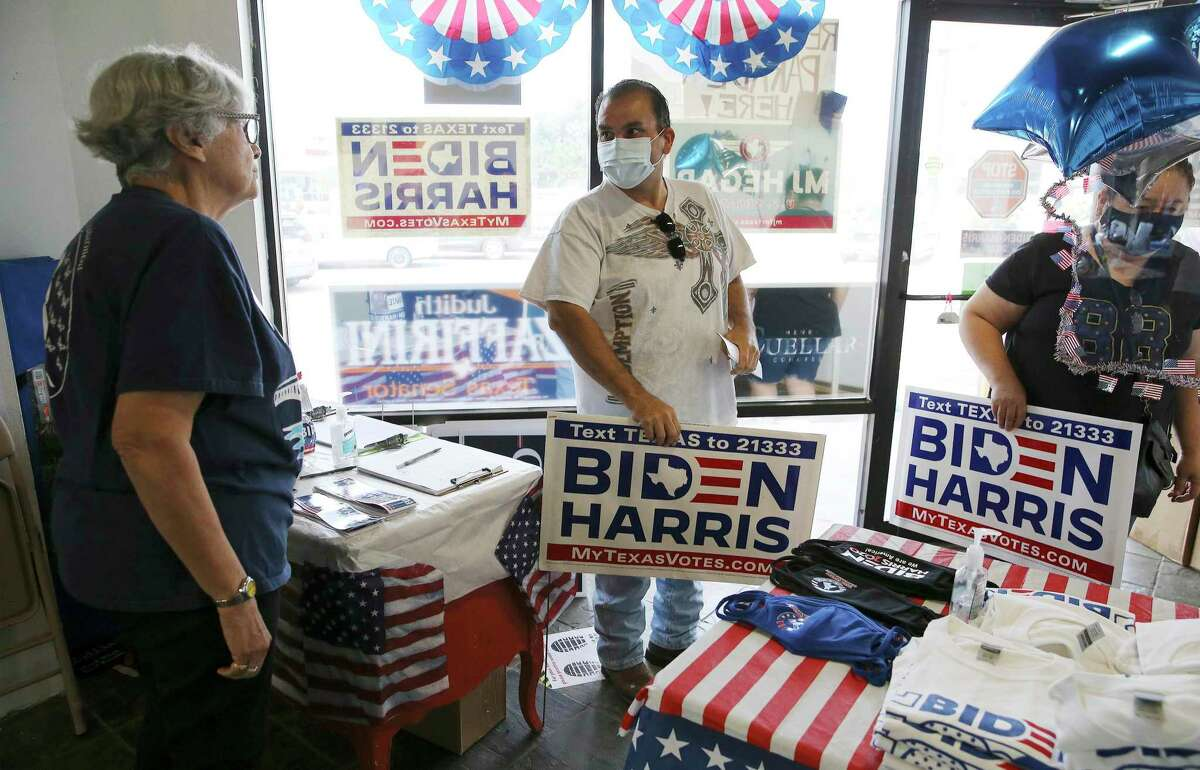 Juan Trevino (center) and his sister, Anna Trevino, pick up the last few Biden-Harris yard signs given to them by Ana Saenz, secretary of the Webb County Democratic Party, at the party headquarters in Laredo on Wednesday, Sept. 23, 2020.