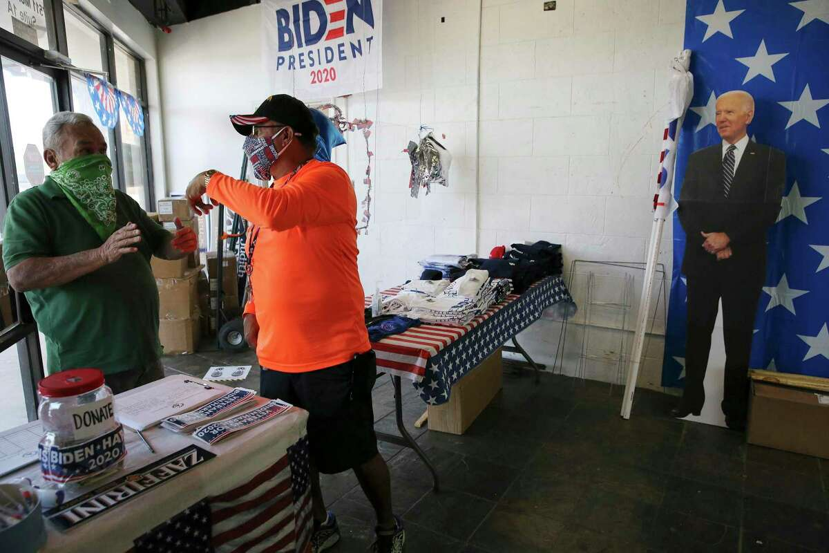 Army veteran and Webb County Democratic Party volunteer John Vargas (second from left) talks with a man at the party headquarters in Laredo on Wednesday, Sept. 23, 2020.