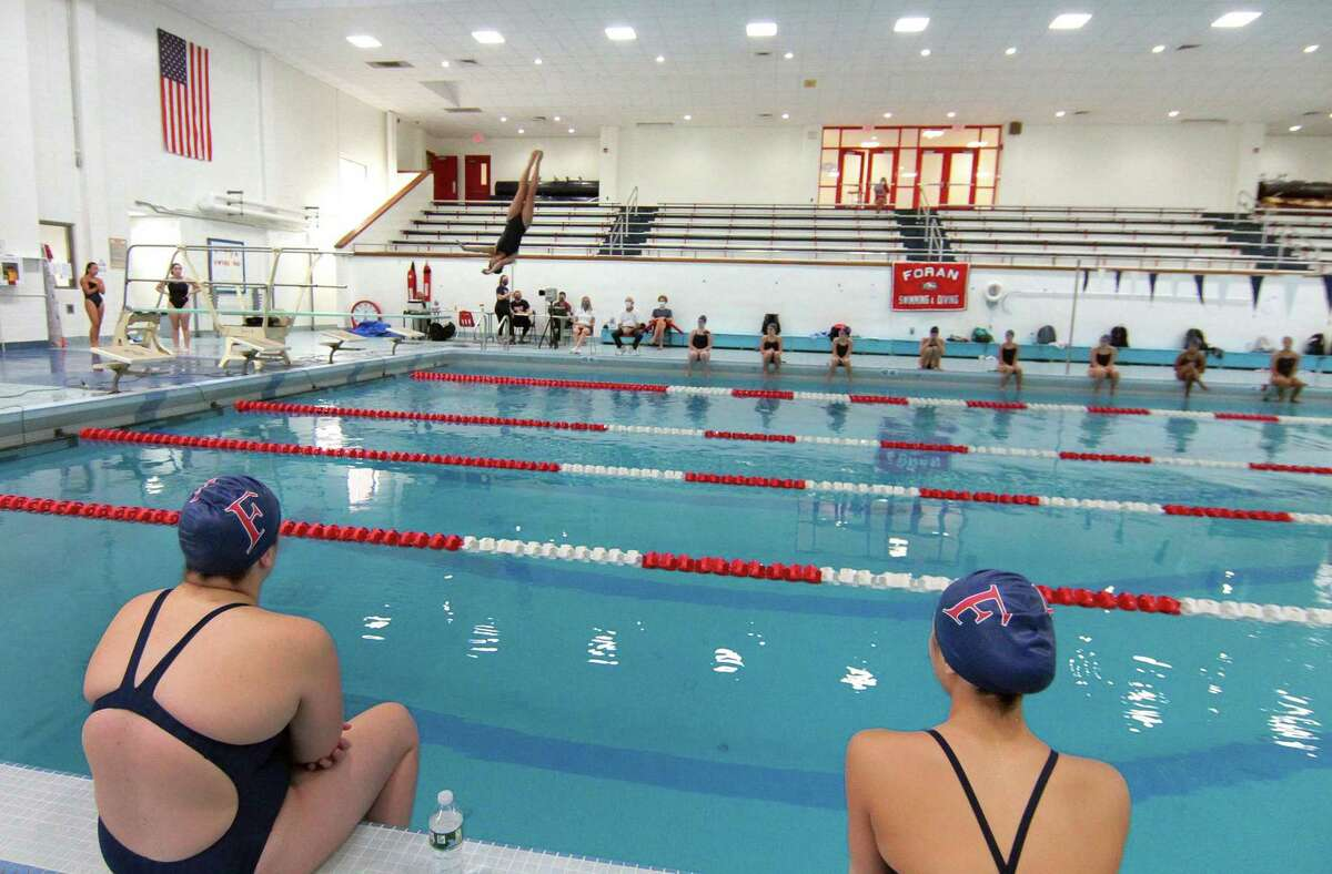 Foran teammates sit apart from each other as diving takes place during a swim meet in Milford on Thursday.