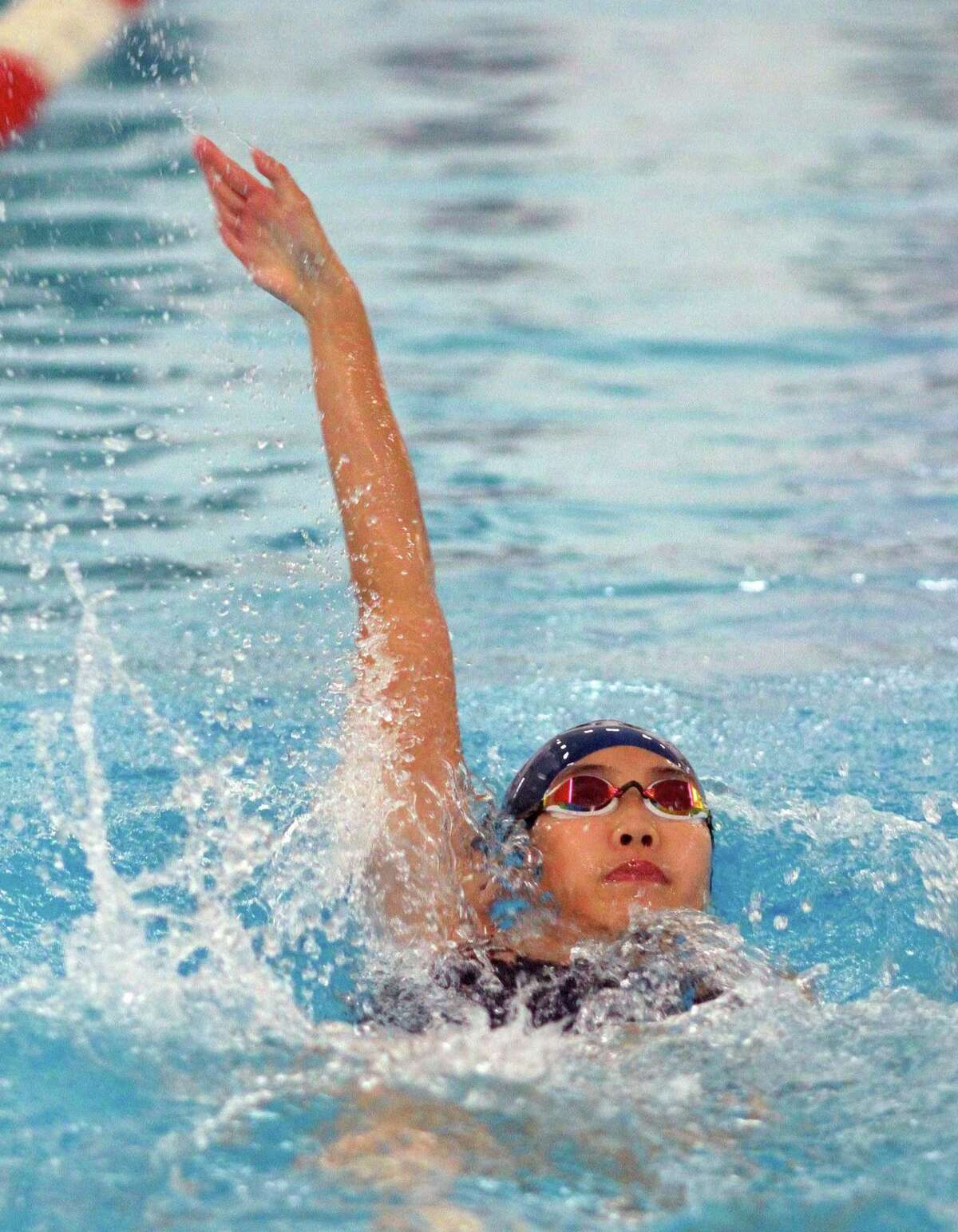 Foran's Ellen Pan does the backstroke during the girls swim meet in Milford on Thursday.
