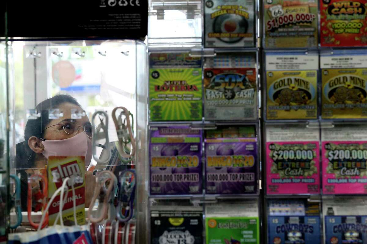 Leticia Morales looks over the inventory as she buys Texas Lottery scratch-off tickets at the Potranco Food Mart on city far northwest side, Thursday, Oct. 1, 2020. The state agency reported $6.704 billion in sales for its 2020 fiscal year ?' Oct. 1, 2019, to Sept. 30 ?' a 7.5 percent increase over the previous year. The store is the number one seller of tickets in the city.