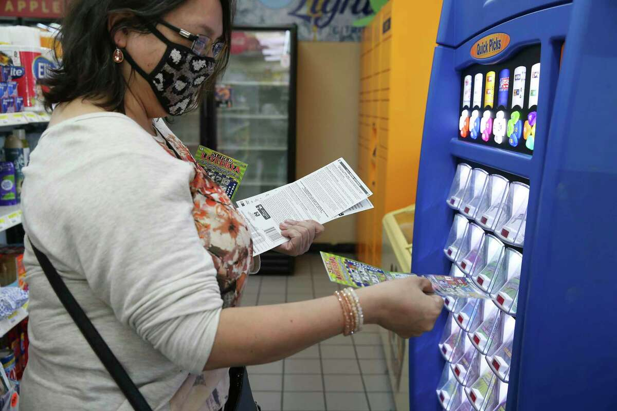 Maribel Fuentes checks her scratch-off tickets in one two kiosks at the Potranco Food Mart on city far northwest side, Thursday, Oct. 1, 2020. The state agency reported $6.704 billion in sales for its 2020 fiscal year ?' Oct. 1, 2019, to Sept. 30 ?' a 7.5 percent increase over the previous year. The store is the number one seller of tickets in the city.