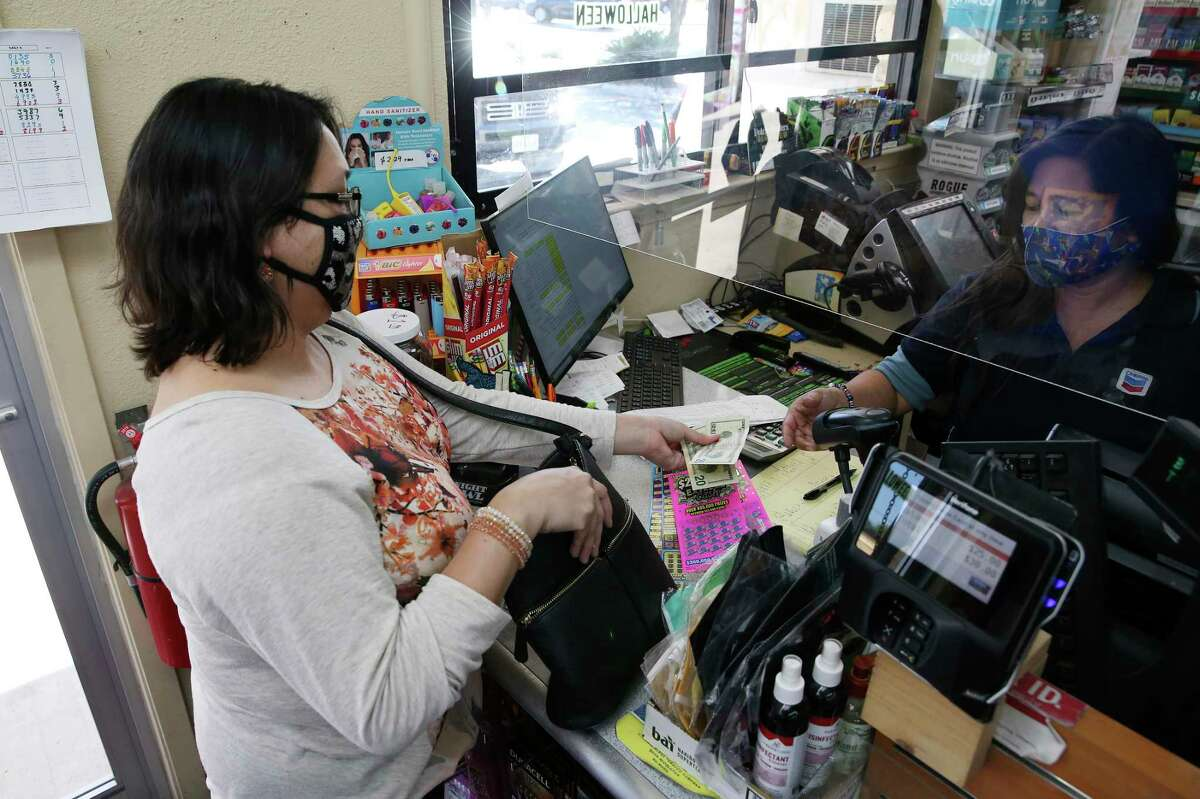 Maribel Fuentes buys scratch-off tickets from Mary Bosea at the Potranco Food Mart on city far northwest side, Thursday, Oct. 1, 2020. The state agency reported $6.704 billion in sales for its 2020 fiscal year ?' Oct. 1, 2019, to Sept. 30 ?' a 7.5 percent increase over the previous year. The store is the number one seller of tickets in the city.