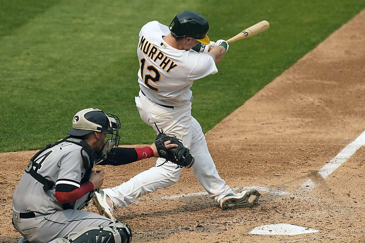 Oakland Athletics' Sean Murphy (12) swings on a two-run home run in front of Chicago White Sox catcher Yasmani Grandal during the fourth inning of Game 3 of an American League wild-card baseball series Thursday, Oct. 1, 2020, in Oakland, Calif. (AP Photo/Eric Risberg)