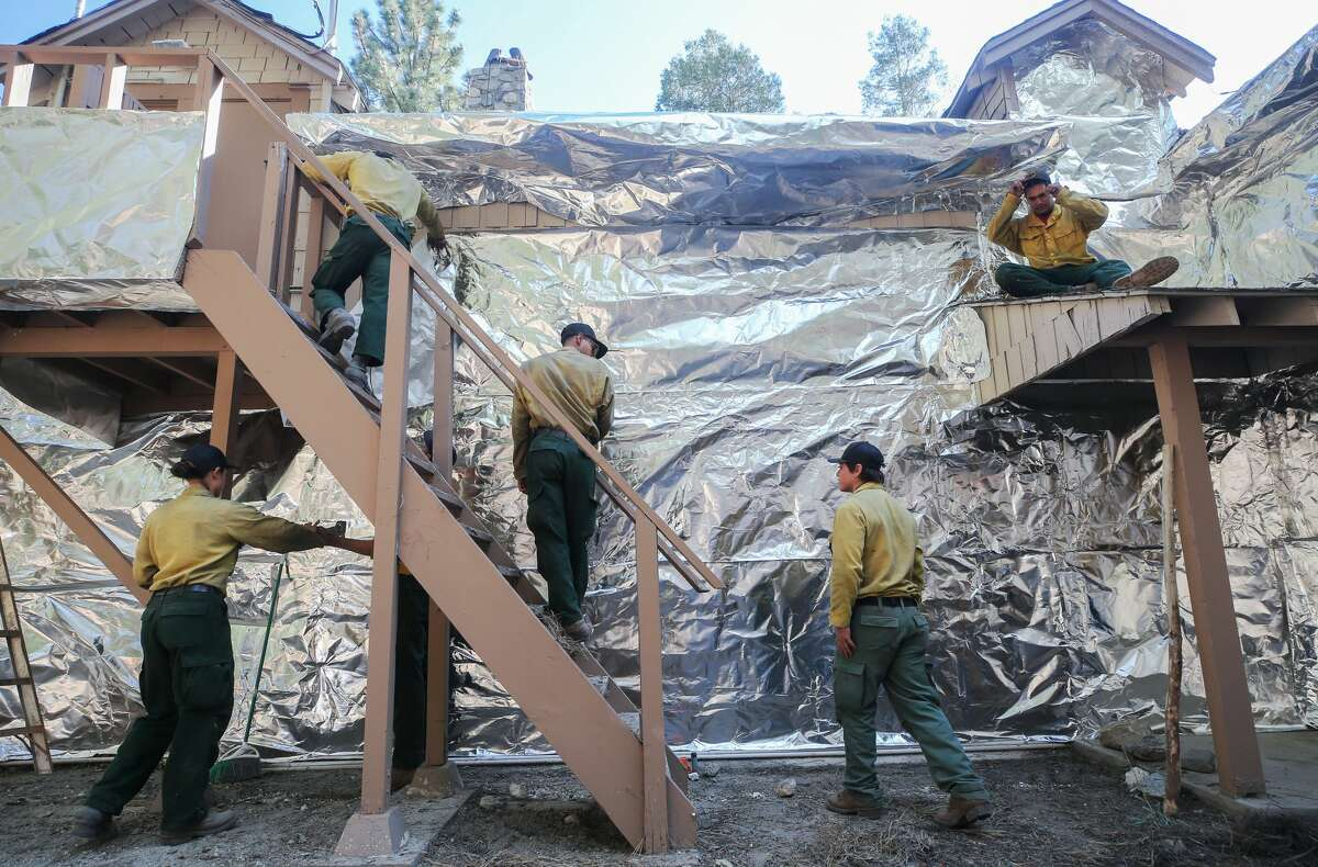 Bear Divide Hotshots firefighters apply structure wrap to a ranger station to protect it from the Bobcat Fire on Sept. 19, 2020, in Wrightwood, Calif. A similar structure wrap was used in Sequoia National Park to protect a historic ranger station from the flames of the SQF Complex.