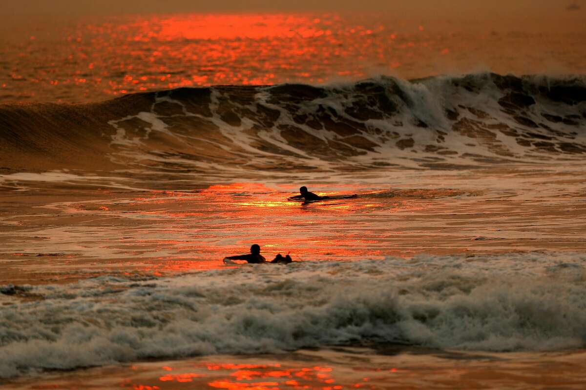Surfers paddle as the sun sets at Rodeo Beach in Sausalito, Calif., on Thursday, October 1, 2020.