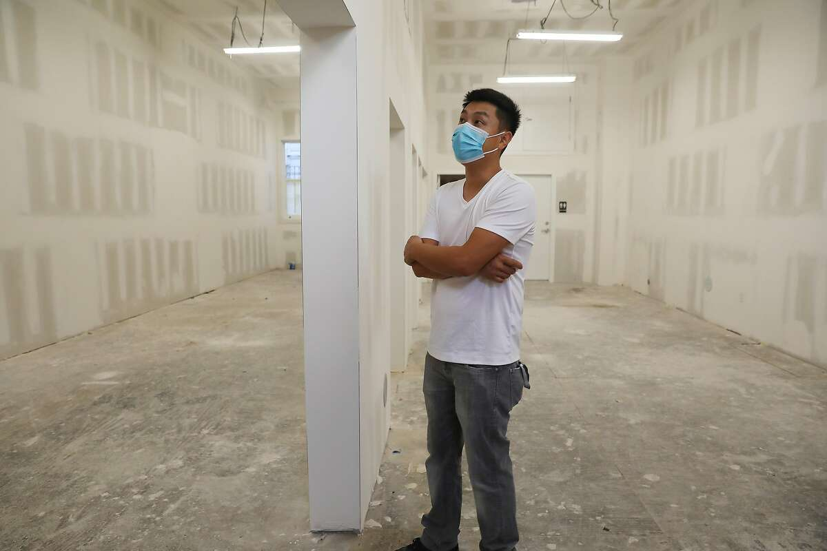 Jason Yu stands in the still-empty commercial space on 20th and Valencia streets that he has been trying to turn into an ice cream shop for 15 months.