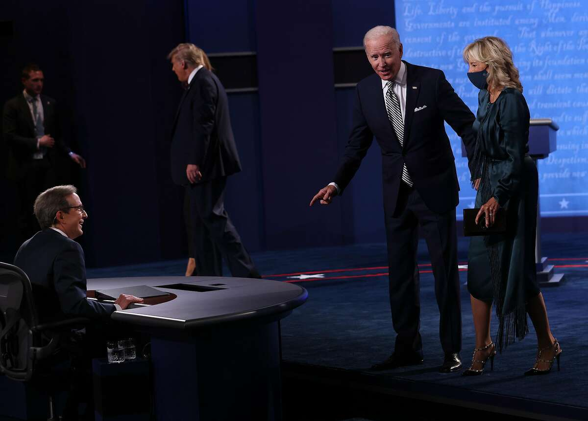 Democratic presidential nominee Joe Biden and his wife, Jill Biden, speak to debate moderator Chris Wallace after the first presidential debate against President Trump (in background) on Tuesday in Cleveland.