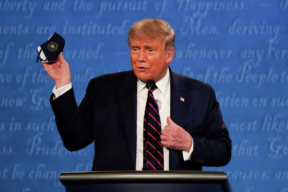 In this Sept. 29, 2020, file photo, President Donald Trump holds up his face mask during the first presidential debate at Case Western University and Cleveland Clinic, in Cleveland, Ohio. President Trump and first lady Melania Trump have tested positive for the coronavirus, the president tweeted early Friday. Photo: Julio Cortez, AP / Copyright 2020 The Associated Press. All rights reserved.