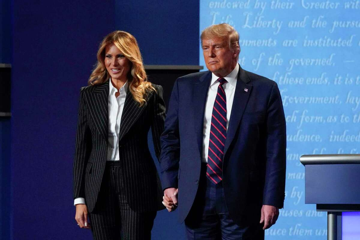 In this Sept. 29, 2020, file photo, President Donald Trump and first lady Melania Trump hold hands on stage after the first presidential debate at Case Western University and Cleveland Clinic, in Cleveland, Ohio. President Trump and First Lady Melania Trump have tested positive for the coronavirus, the president tweeted early Friday.