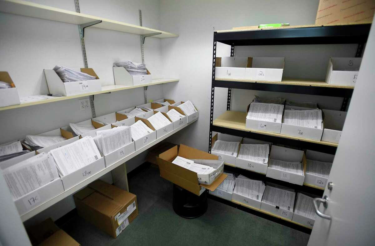 A closet with trays of absentee ballot requests waits for a group of volunteers to process them for the upcoming 2020 elections.