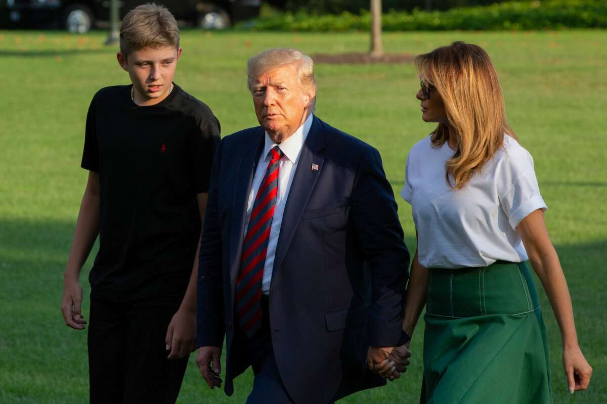 (FILES) In this file photo taken on August 18, 2019, US President Donald Trump (C) First Lady Melania Trump (R) and their son Barron Trump (L) return to the White House after two weeks spent at Trump's golf club in New Jersey, in Washington, DC. - Barron Trump, 14, has tested negative for the coronavirus after both his parents tested positive, a spokeswoman said on October 2, 2020. (Photo by Alastair Pike / AFP) (Photo by ALASTAIR PIKE/AFP via Getty Images)