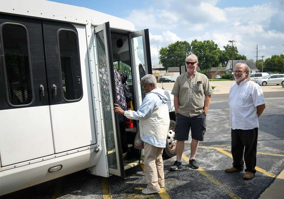 Rider Mary Nunn, left, boards a Main Street Community Center bus as drivers Karl Krachenberg, middle, and Bob Werner look on. Photo: For The Intelligencer